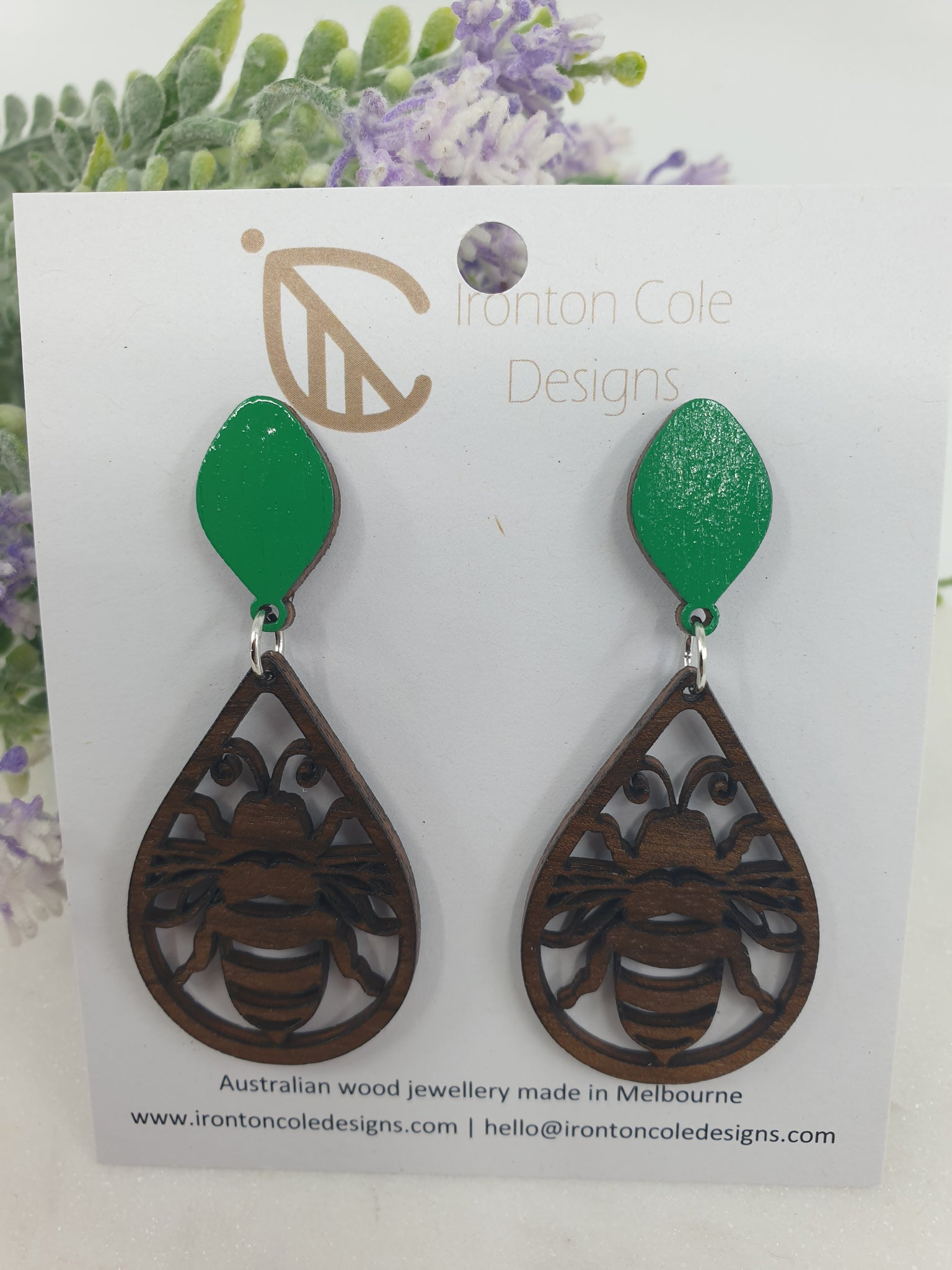 Wooden bee earrings made from queensland walnut and paired with a bright pop of green tear drop post.
