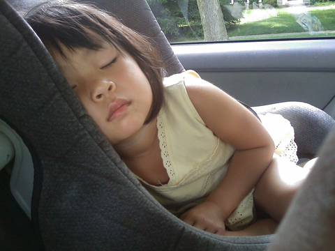 A toddler sleeping in her car seat.
