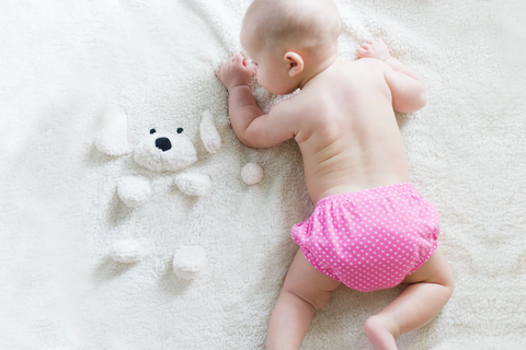 A top-down view of a baby crawling on a white puppy blanket.
