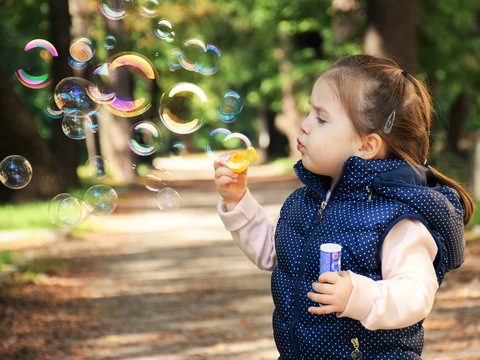 A little girl blowing bubbles outside.
