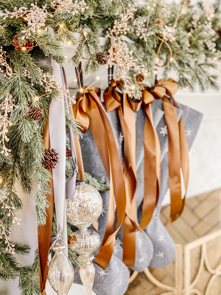 Ashley Childers, linen stockings with satin ribbon on mantel with cedar garland