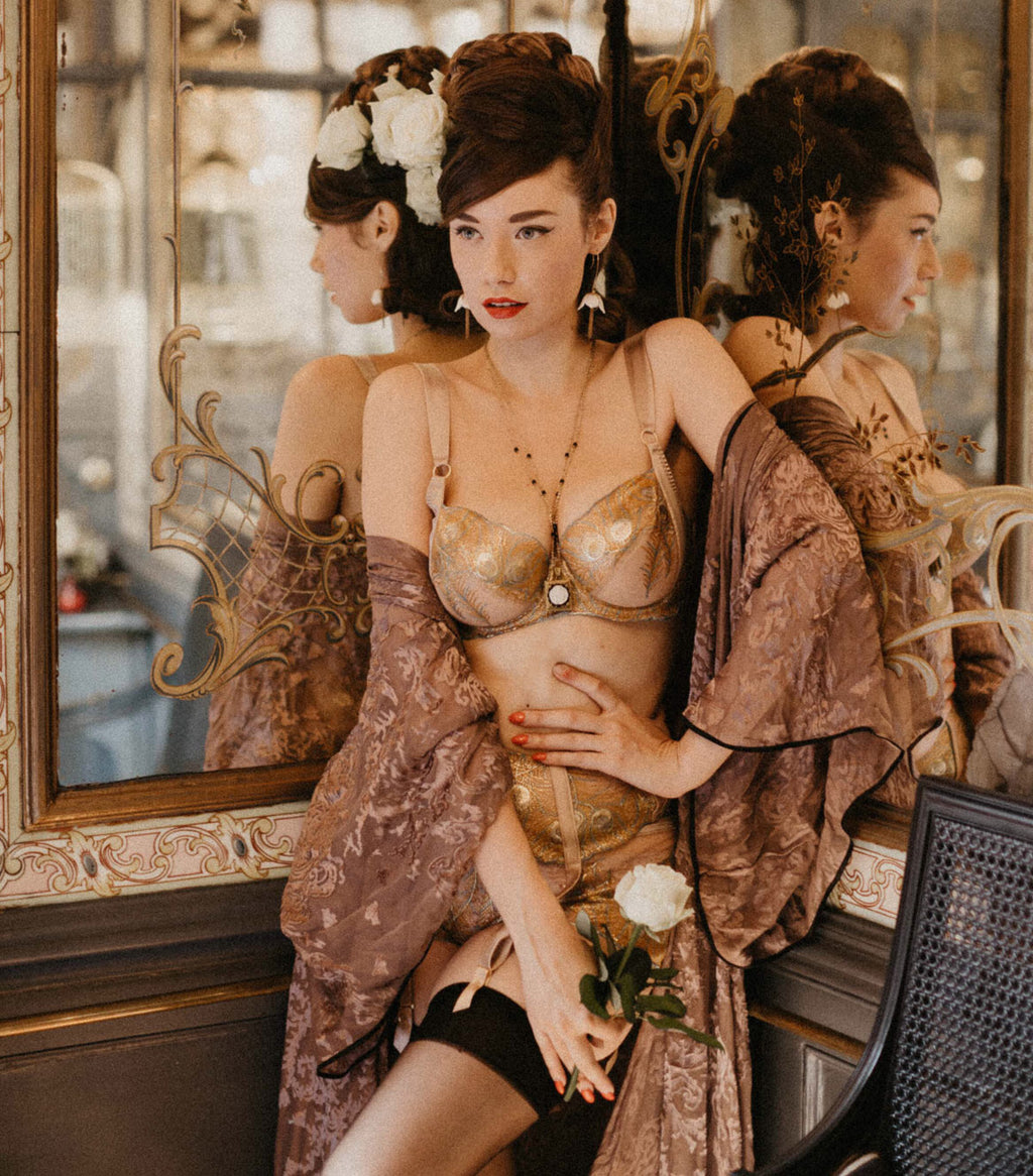 Pinup model Alba Banana wears gold lingerie and sheer robe