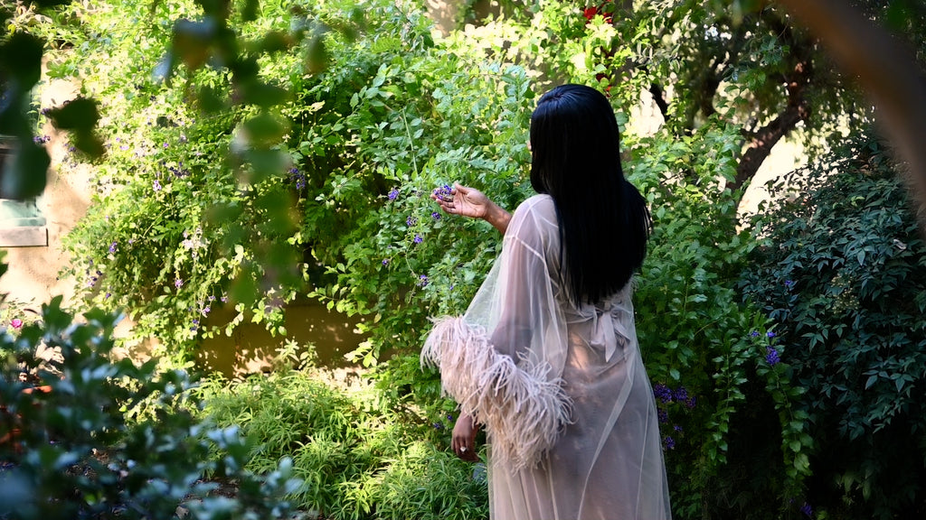 Krystle in garden wearing sheer floor length robe with feather trim