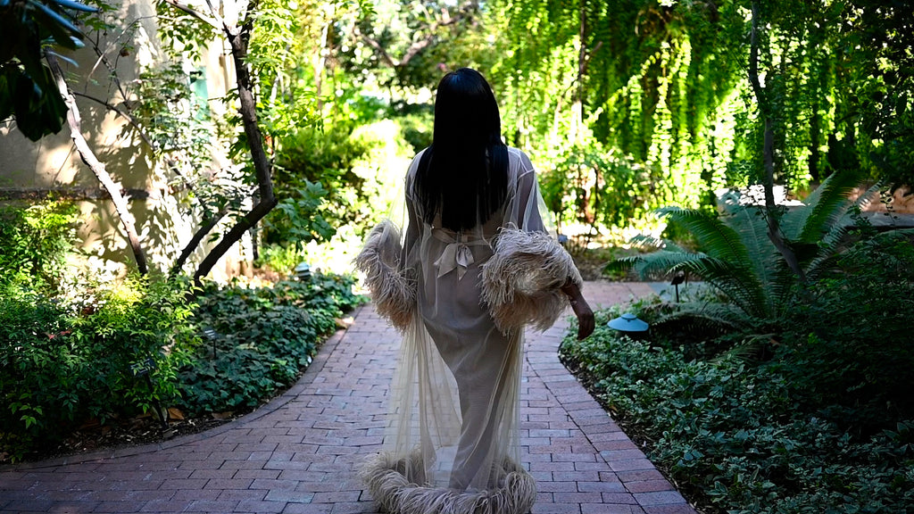 Krystle wearing sheer feather robe and gown in botanical garden