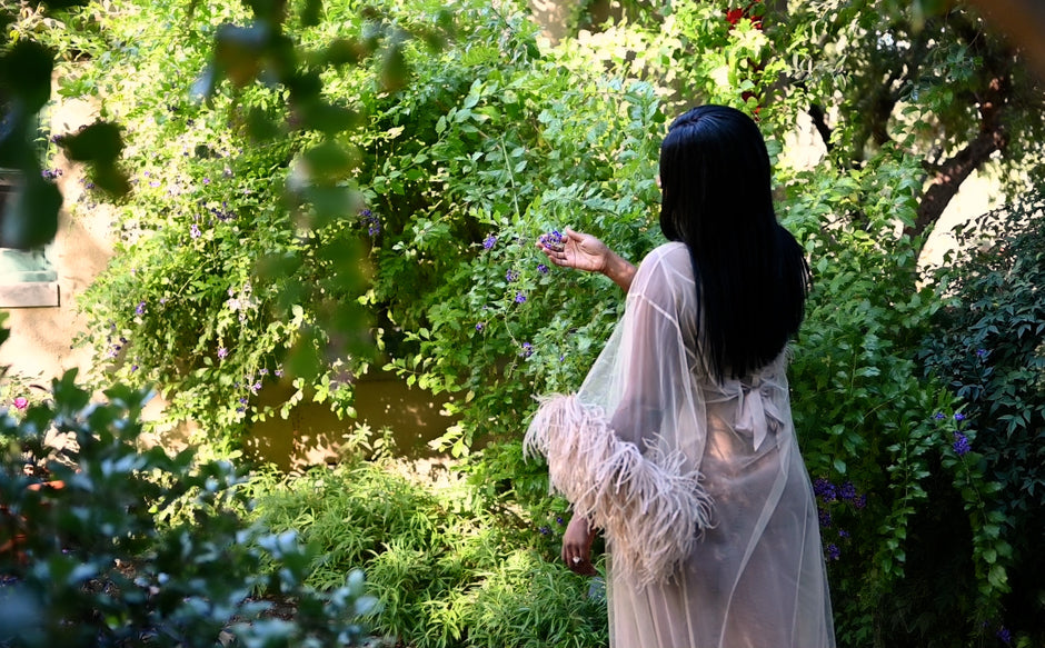 Poet Krsytle Ada Epum in garden wearing feather trimmed gown