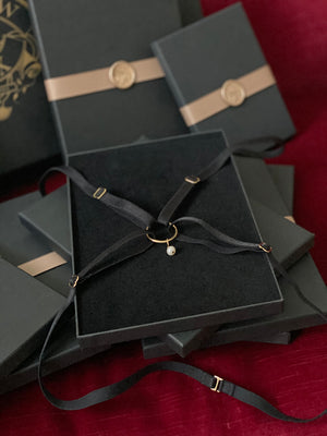Black strapping harness with pearl in velvet gift box