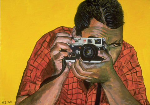 Focus by Yvonne Callaway Smith. A n image of a man taking a photograph with the camera obsucring his face. He stands out against a bright yellow background.