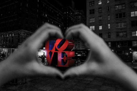 Love by Barry Khan. Black and white photograph of a street scene in the background with hands forming a heart shape in the foreground around the work 'Love' in red.