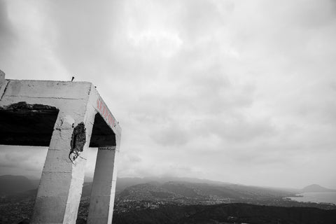 "No Trespassing by Barry Khan. Black and white photograph of a concrete ruin with the words ""Keep Off"" in red and a sprawling city on the mountains in the background."