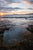 Pebble Pool by Barry Khan. Colour photograph of a small tidal pool on the beach with a sunseting the background.