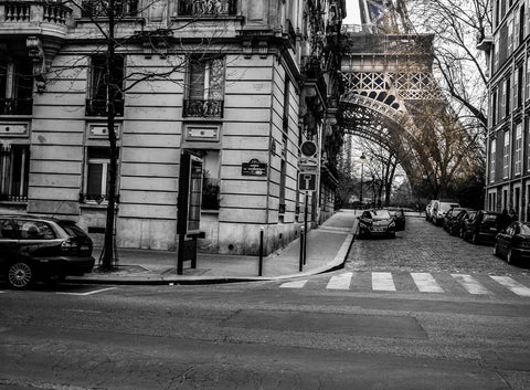 Peeking Paris by Barry Khan. Black and white photograph of a Paris street scene and the foot of the Eiffel Tower in muted colour seen between two buildings.