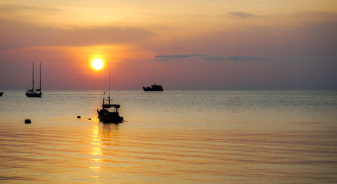 Setting Thailand by Barry Khan. Colour photograph of a sunset over the ocean and sailboats.