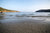 Step Right In by Barry Khan. Colour photograph of a beach with an inlet and rolling hills on either side.