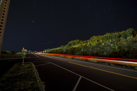 Tail Lights to Paradise by Barry Khan. Colour photograph of a road way with a starry night sky and and moving tail lights.