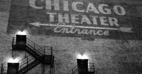 "This Way To The Show by Barry Khan. Black and white photograph of the building with writing on it saying ""Chicago Theater Entrance"" and an arrow."