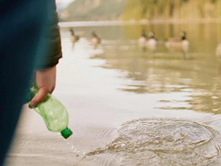 A person picking up plastic out of a lake.