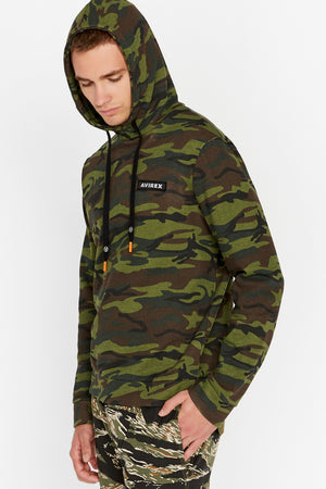 Side view of men wearing a green camo print hoodie sweatshirt with patch on the chest