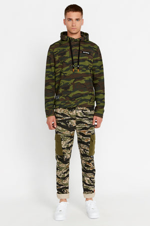 Full view of men wearing a green camo print hoodie sweatshirt with patch on the chest and patch on right bottom and green camo print pants