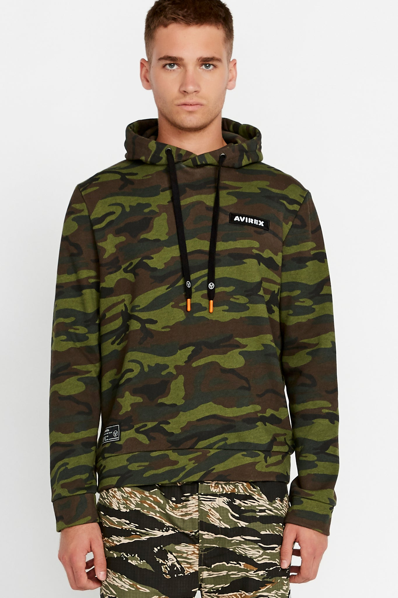 Men wearing a green camo print hoodie sweatshirt with patch on the chest and patch on right bottom