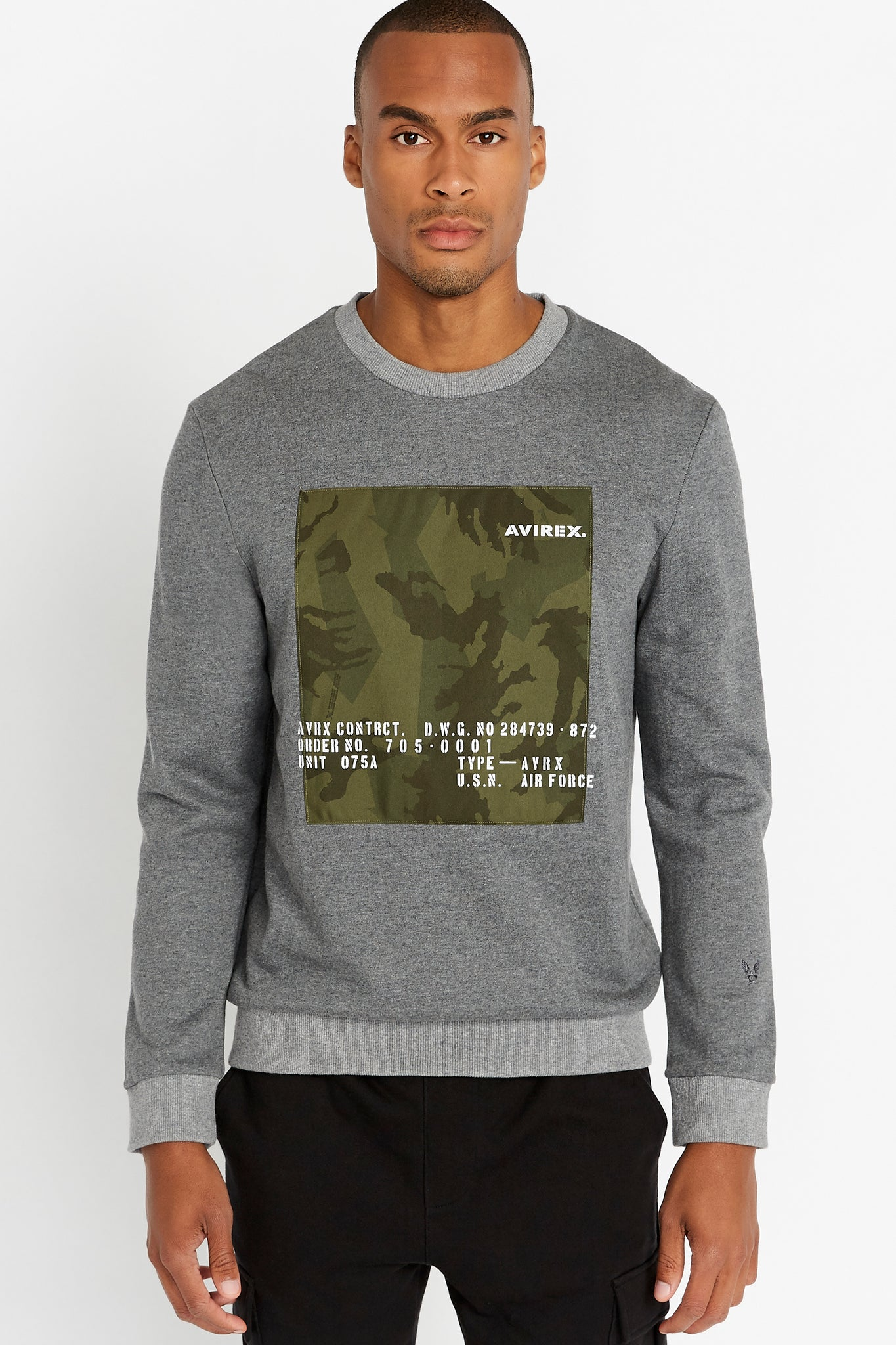 Men wearing a grey long sleeve crew neck sweater with front camo graphics and wing-star embroidery on left sleeve