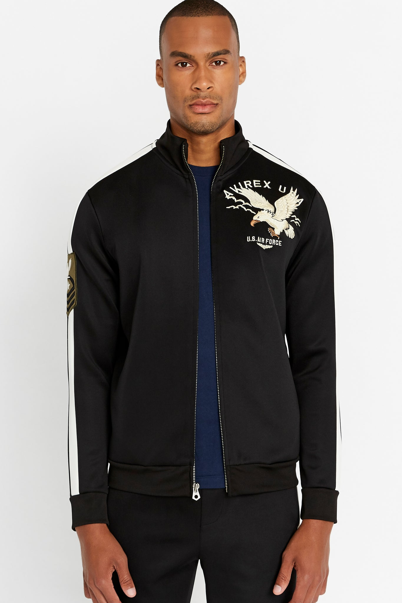 Front view of men wearing an open black jet track jacket with eagle embroidery on the chest