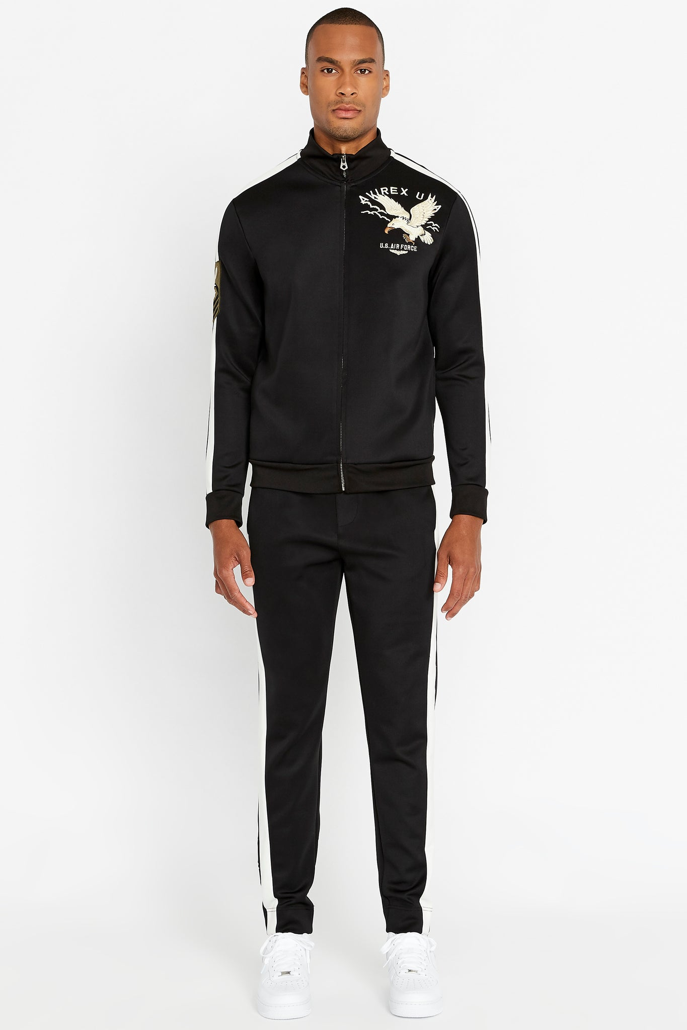 Full view of men wearing a fully zipped black jet track jacket with eagle embroidery on the chest and black pants