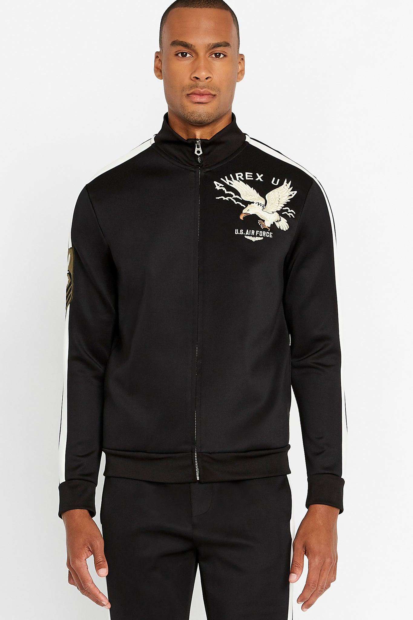 Front view of men wearing a fully zipped black jet track jacket with eagle embroidery on the chest
