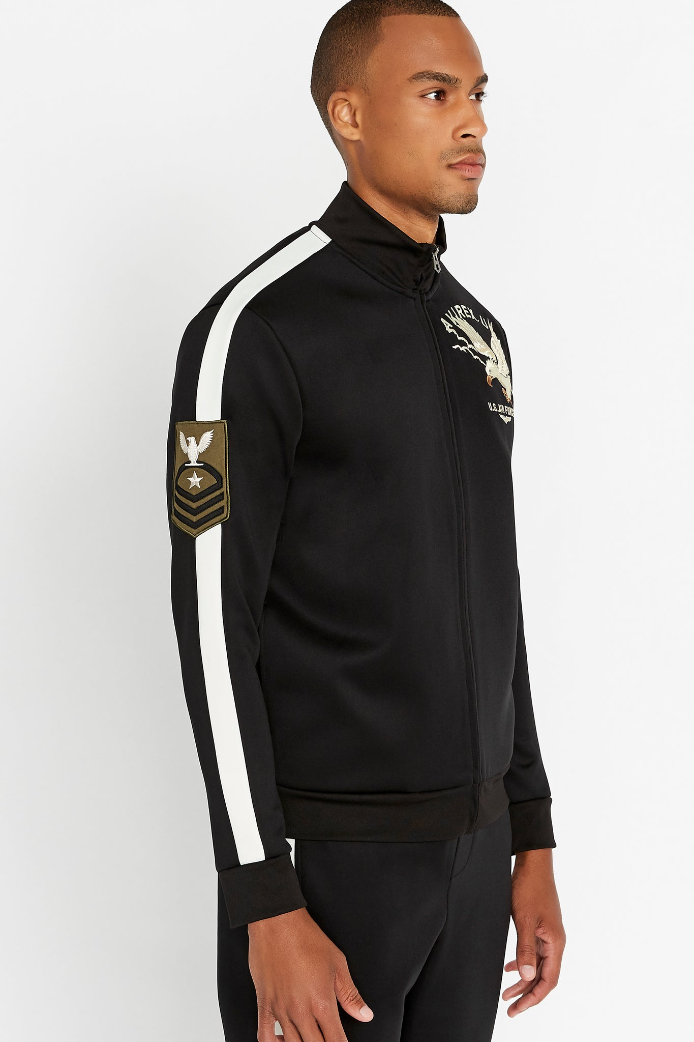 Side view of men wearing a fully zipped black jet track jacket with eagle embroidery on the chest and bold white side strip on the right sleeve