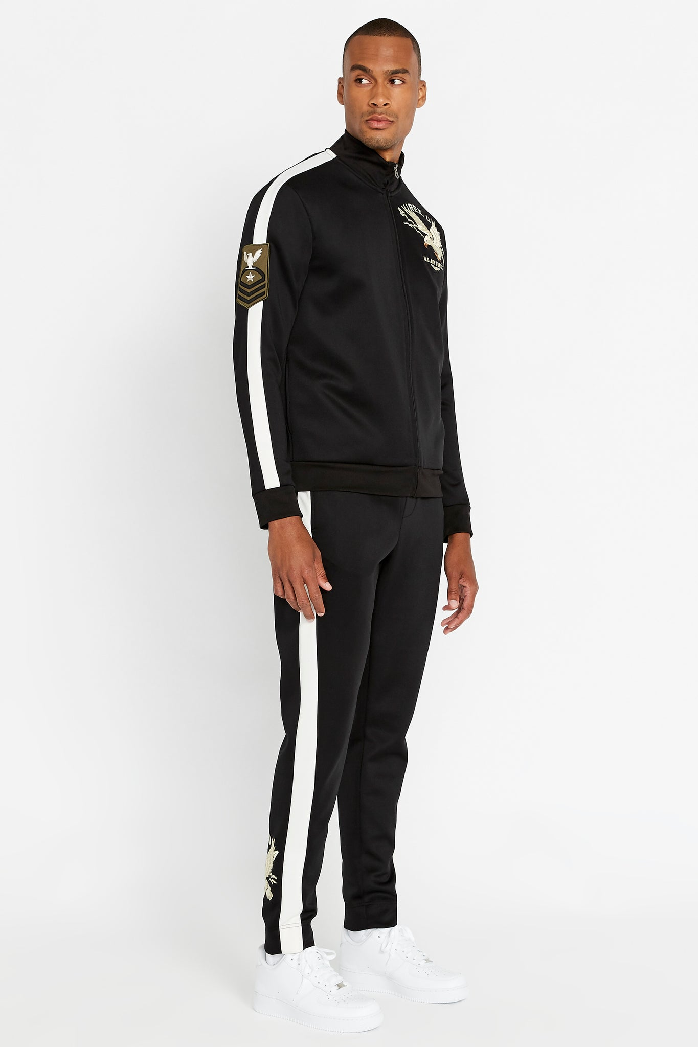Full side view of men wearing a fully zipped black jet track jacket with eagle embroidery on the chest and bold white side strip on the right sleeve and black pants