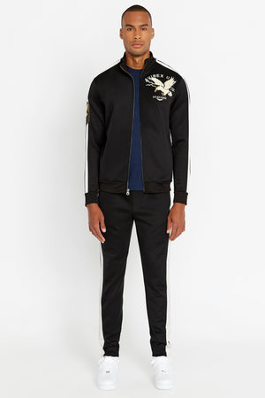 Full view of men wearing an open black jet track jacket with eagle embroidery on the chest and black pants