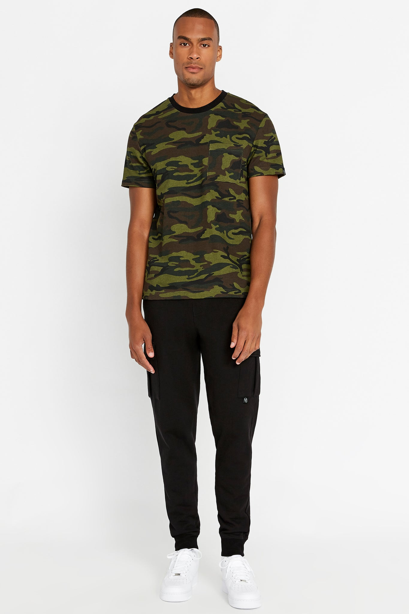 Full view of men wearing a camo print short sleeve crew T-shirt with chest pocket and black pants