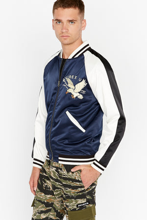 Side view of men wearing a fully zipped three-tone satin bomber jacket with two pockets on sides and eagle embroidery on the chest, navy on the body and white on the sleeve with black stripe