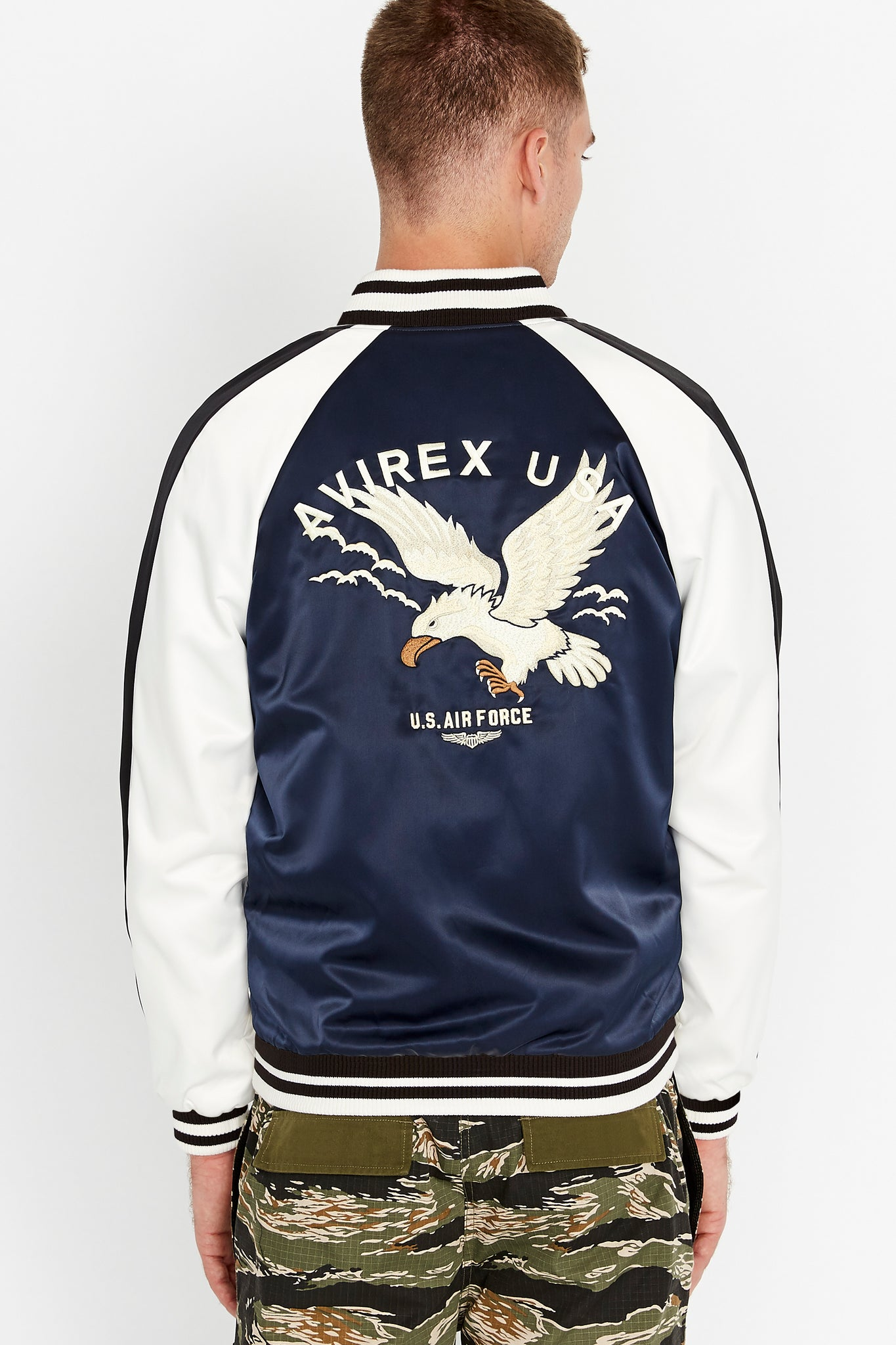Back view of men wearing a three-tone satin bomber jacket with eagle embroidery on the back, navy on the body and white on the sleeve with black stripe