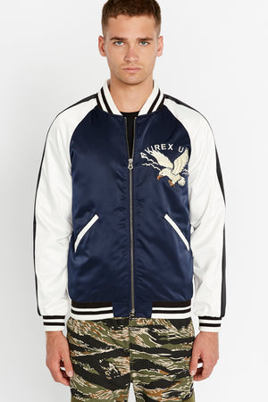 Front view of men wearing a fully zipped three-tone satin bomber jacket with two pockets on sides and eagle embroidery on the chest, navy on the body and white on the sleeve with black stripe