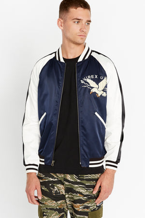 Front view of men wearing an open three-tone satin bomber jacket with two pockets on sides and eagle embroidery on the chest, navy on the body and white on the sleeve with black stripe