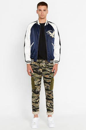 Full front view of men wearing an open three-tone satin bomber jacket with two pockets on sides and eagle embroidery on the chest, navy on the body and white on the sleeve with black stripe and green camo printed pants