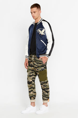 Full side view of men wearing an open three-tone satin bomber jacket with two pockets on sides and eagle embroidery on the chest, navy on the body and white on the sleeve with black stripe and green camo printed pants
