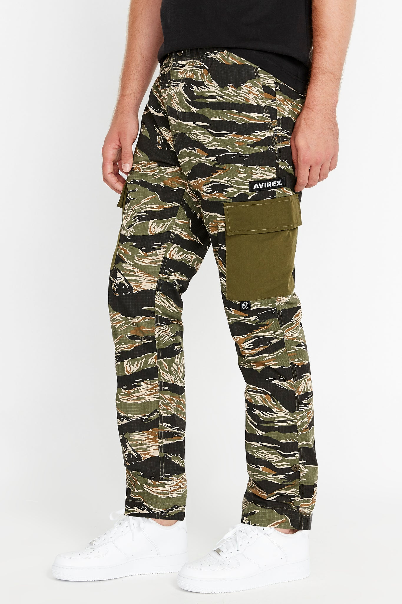 Side view of tigerstripe camo print pants with Avirex patch above side cargo pocket in solid color