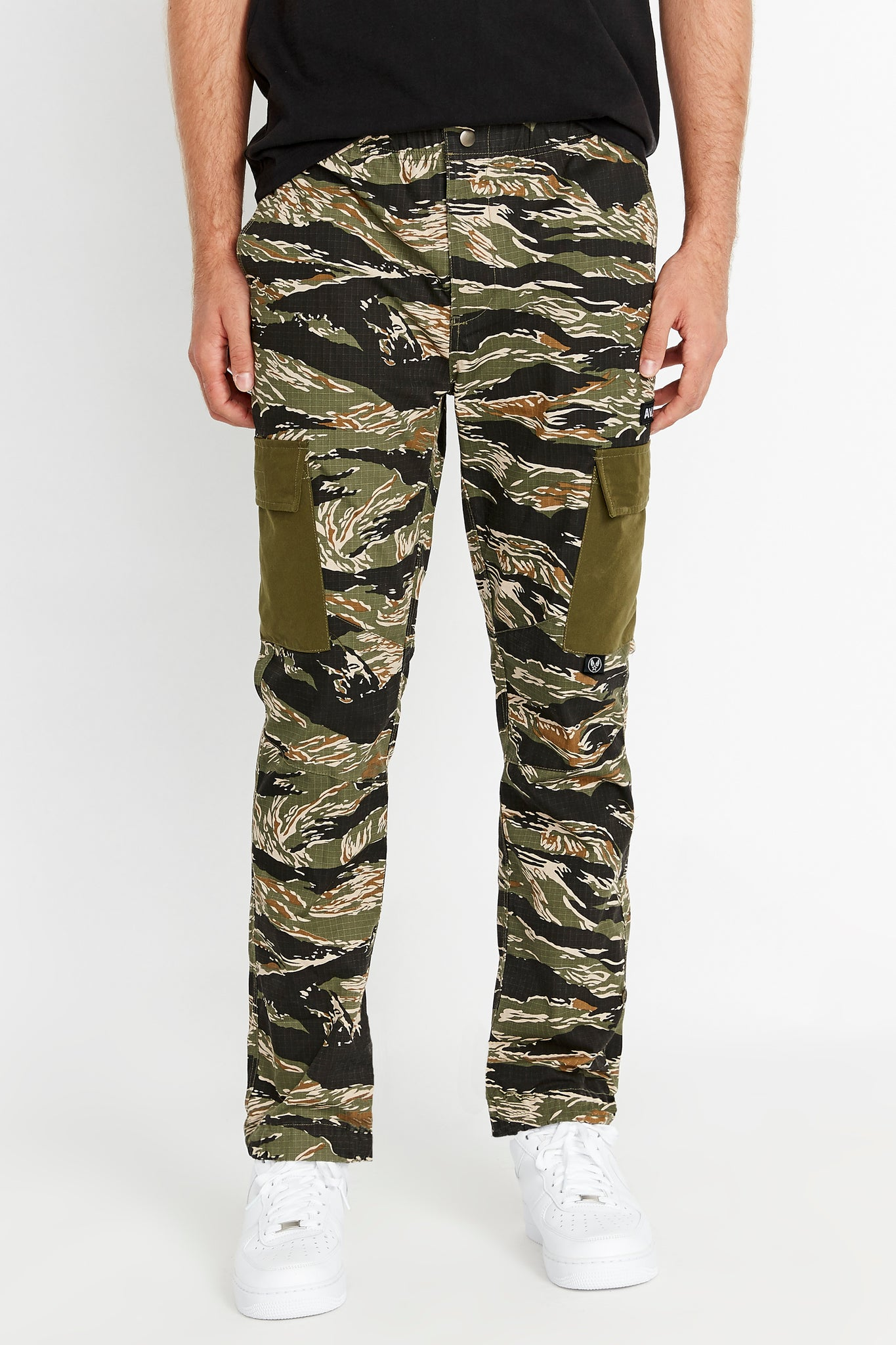Front view of tigerstripe camo print pants with side cargo pockets in solid color