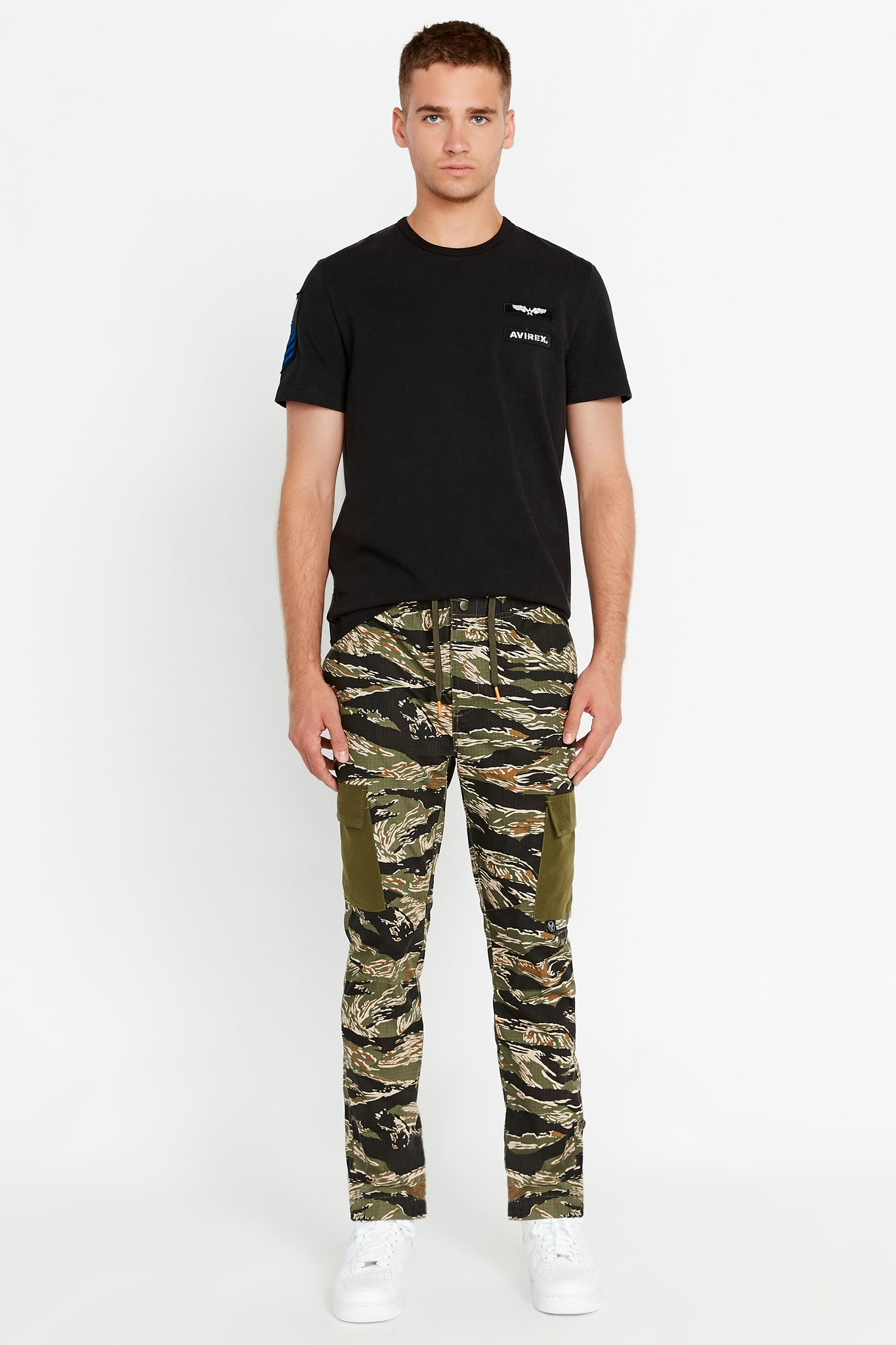 Full view of men wearing a tigerstripe camo print pants with side cargo pockets in solid color and black short sleeve crew neck T-Shirt