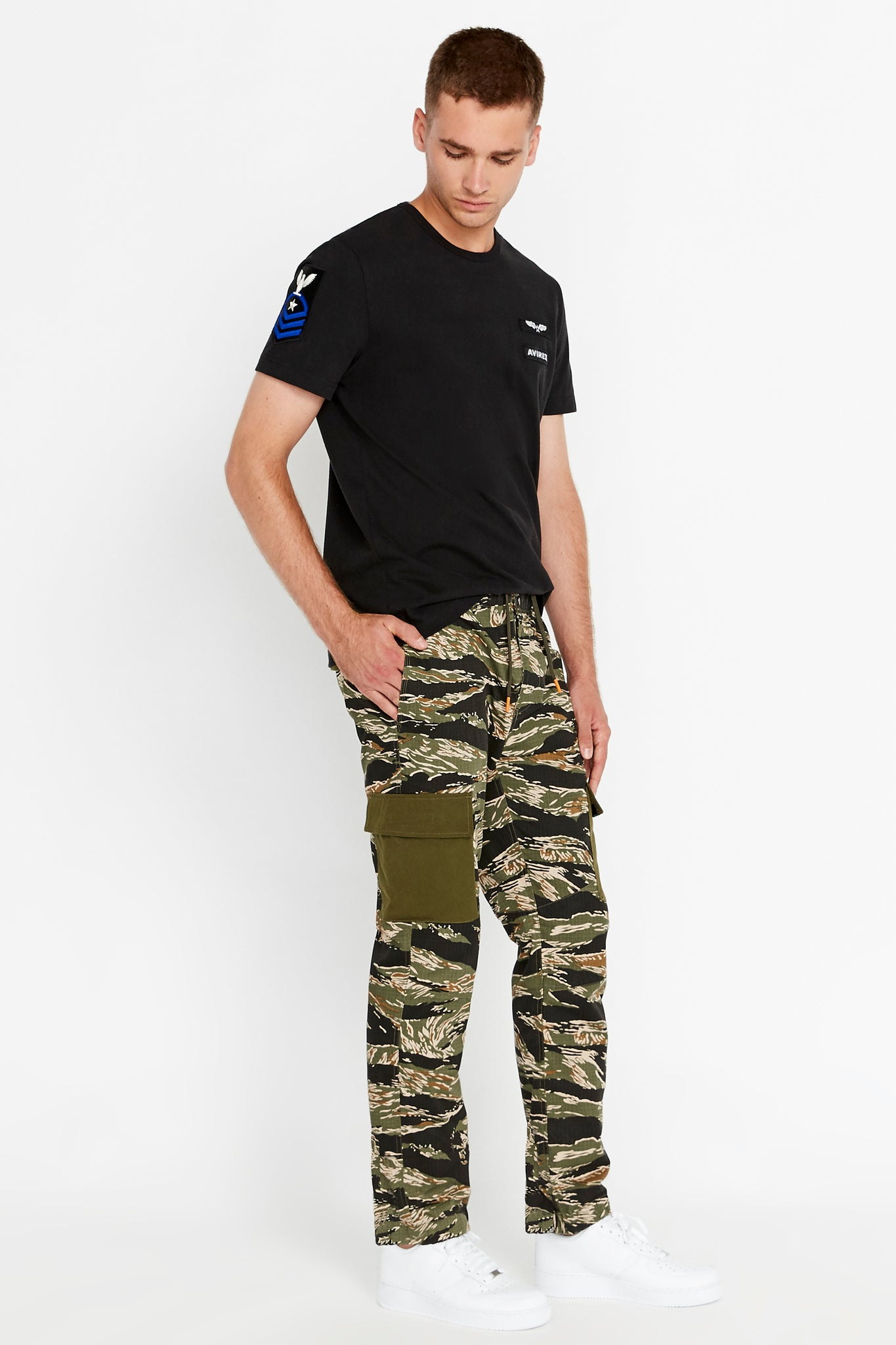 Side full view of men wearing a tigerstripe camo print pants with side cargo pockets in solid color and black short sleeve crew neck T-Shirt