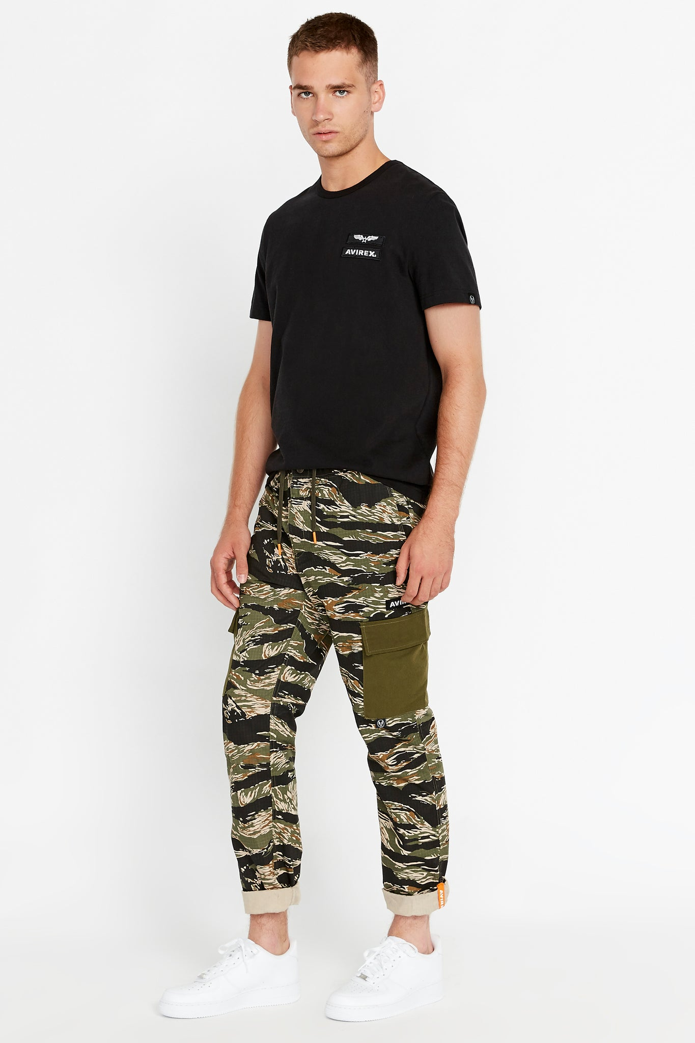Side full view of men wearing a tigerstripe camo print pants with side cargo pockets in solid color and black short sleeve crew neck T-Shirt, rolled up hem with reflective logo