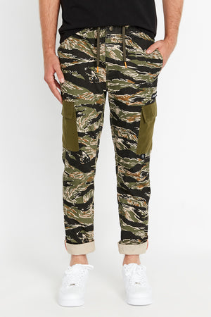 Front view of tigerstripe camo print pants with side cargo pockets in solid color.  Rolled up hem with reflective logo