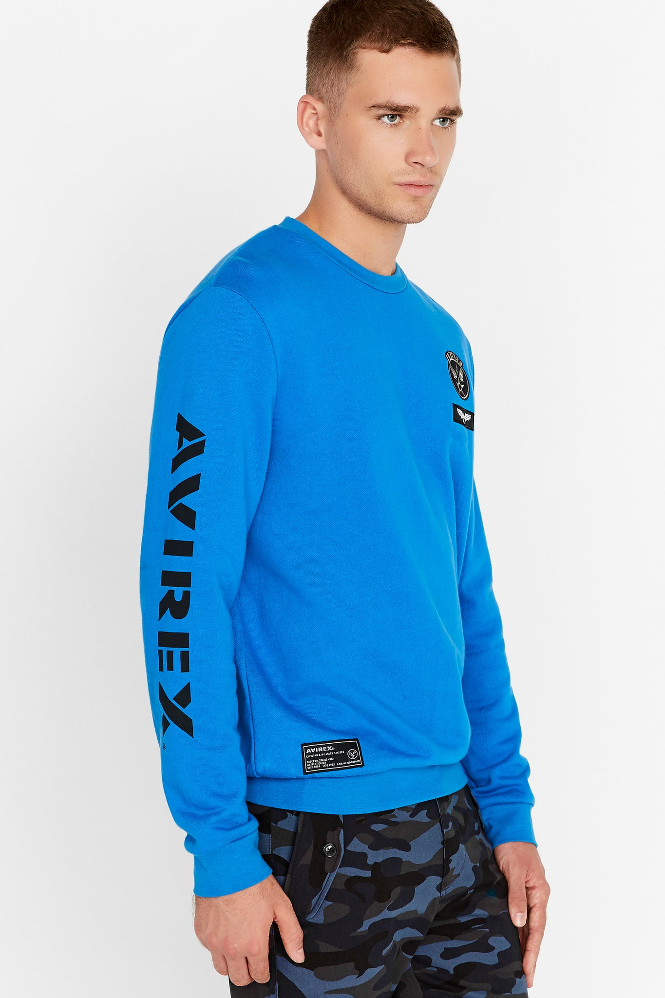 Side view of men wearing a blue long sleeve crew neck sweater with patches on the chest and right bottom and logo print on the right sleeve