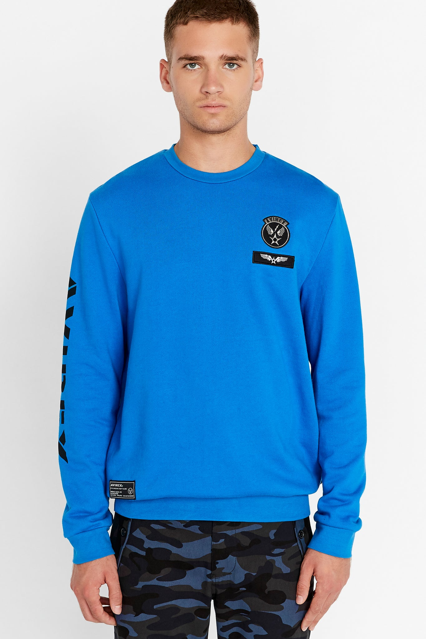 Men wearing a blue long sleeve crew neck sweater with patches on the chest and right bottom and logo print on the right sleeve