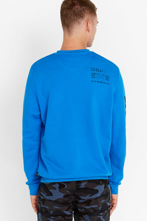 Back view of men wearing a blue long sleeve crew neck sweater with text print on the back shoulder