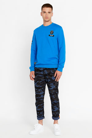 Full view of men wearing a blue long sleeve crew neck sweater with patches on the chest and right bottom and logo print on the right sleeve and blue camo print pants
