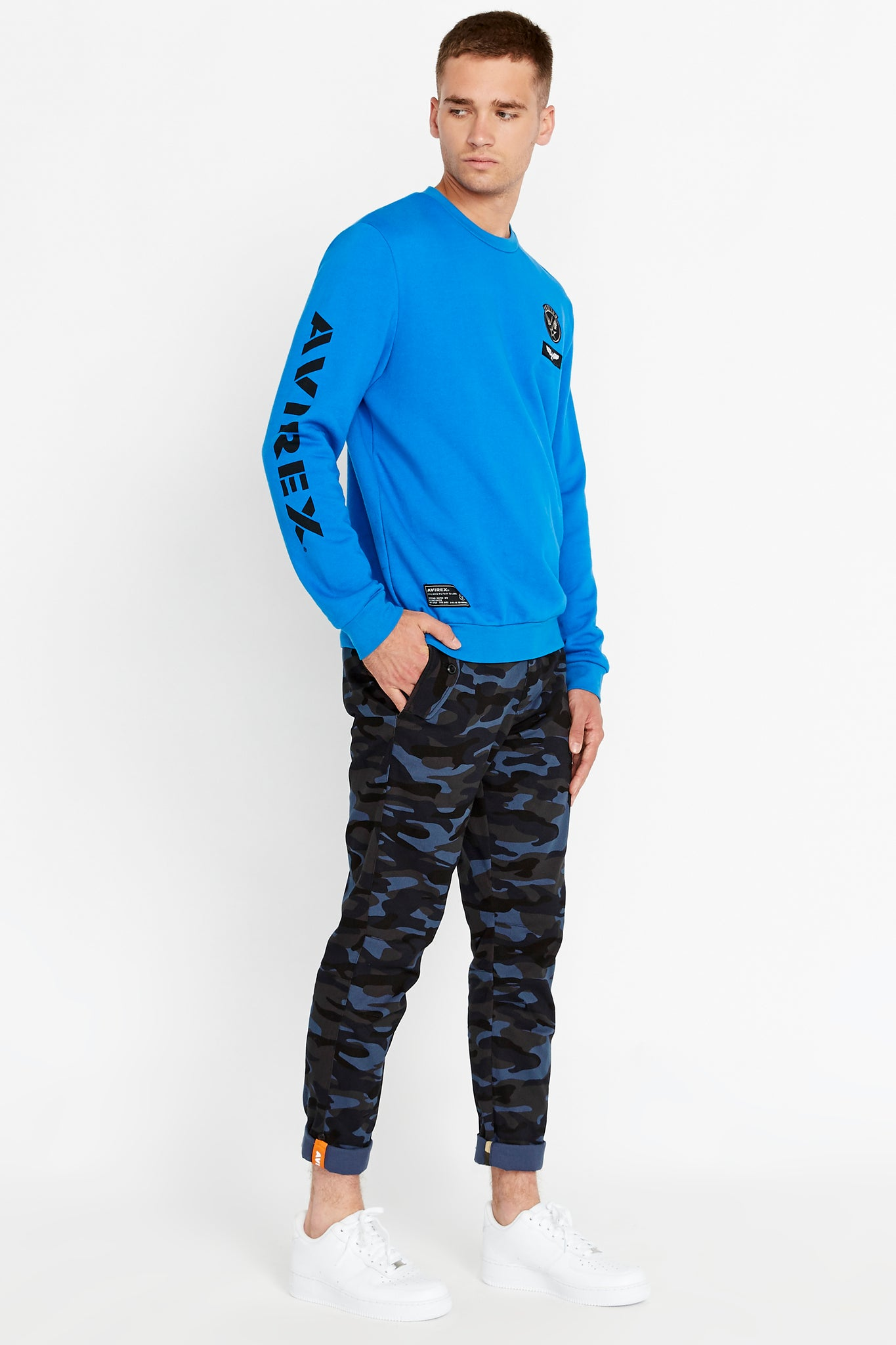 Side full view of men wearing a blue long sleeve crew neck sweater with patches on the chest and right bottom and logo print on the right sleeve and blue camo print pants