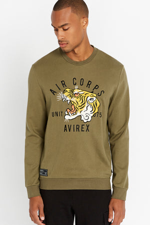 Men wearing an olive long sleeve crew neck sweater with front tiger embroidery and patch on right bottom