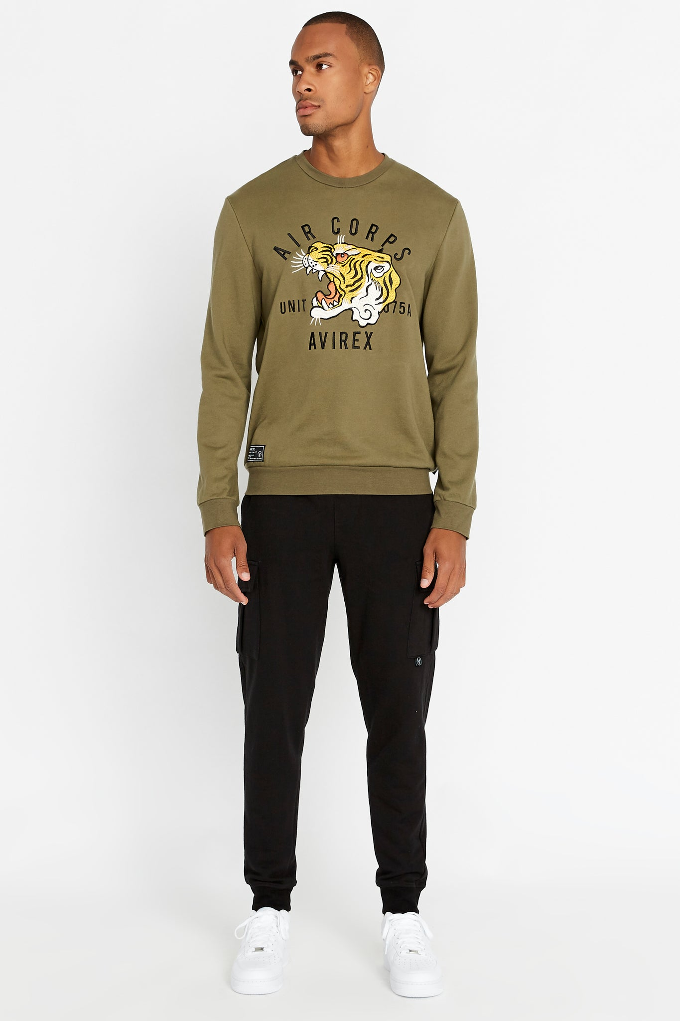Full view of men wearing an olive long sleeve crew neck sweater with front tiger embroidery and patch on right bottom and black pants